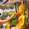 photo: Songkran Buddha Cleansing - A Thai woman at Wat Pho temple rinses a Buddha statue, part of the festival tradition for every Thai new year.