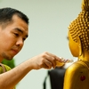 Scented Statue Photo: A Thai man gently pours a small bottle of perfume onto a Buddha statue for Songkran.