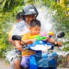 Songkran Festival, Thai New Year Photo: A direct hit lands on a motorcycling Dad and his unprotected kids during Songkran water fights.