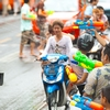 Songkran Bus Assault Photo: Innocent motorcyclists are caught in the crossfire of a watery battle with a bus during Songkran water festival.