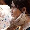 Songkran Pasted People Photo: A young Thai woman receives a gentle application of talcum powder paste from a stranger during Songkran.