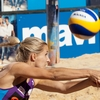 Double Threat Photo: A women's beach volleyball player returns a high-speed spiked ball.