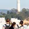 Opposite Overlook Photo: Tourists photographing Coit Tower from the top of Lombard Street in San Francisco.