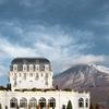 Rich Retreat Photo: A side-view of the Hotel Imperial Palace, a lakeside casino, with the mountains of Annecy, France in the background.
