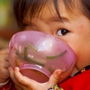 Dubious Deadeye Photo: A young Chinese girl plants her face in her food bowl while keeping a wary eye on the photographer (ARCHIVED PHOTO on the weekends - originally photographed 2007/09/30).